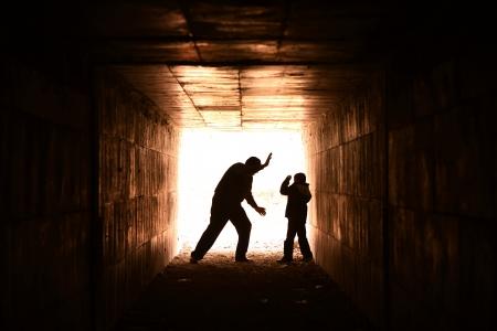 maltrato infantil: hombre sin hogar en el callejón que comprime la parte inferior del niño Foto de archivo