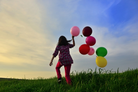 young girl playing with balloons photo