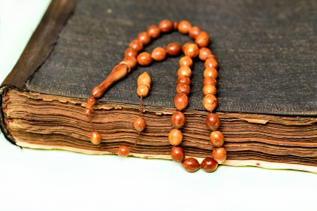 establishing: An ancient hand scripted Quran with prayer beads