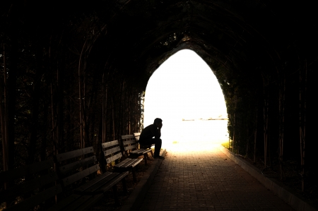 suffering: young sad sitting in the dark tunnel