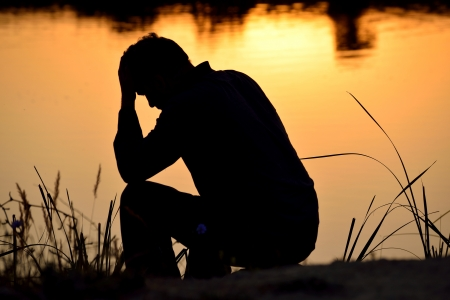 depressed man sitting against the light reflected in the water Stock Photo