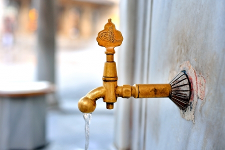 Antique Turkish faucet on wall photo