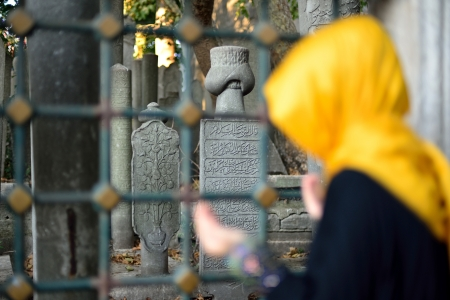 veiled woman praying in front of the old tombstones photo