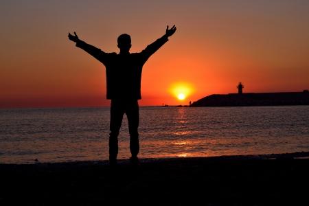 Silhouette der jungen stehend am Strand bei Sonnenuntergang