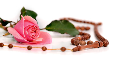 Islamic prayer beads and a rose on a white background