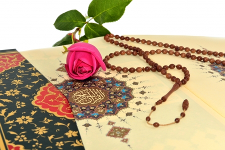 islamic prayer: Muslim rosary beads and rose on the Holy Quran