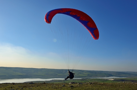 paraglider soar in the air amid wondrous landscape Stock Photo - 25286918