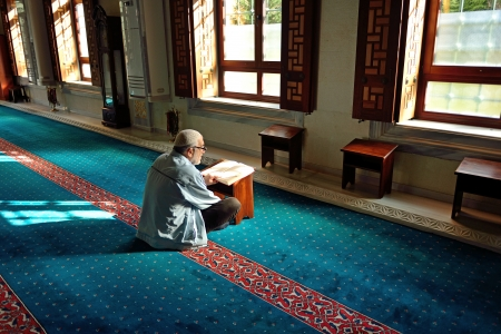 establishing: ISTANBUL, TURKEY - 19 JANUARY  Unknown man in the Tunahan Mosque a read Quran in Istanbul, Turkey on january 19, 2014  Tunahan mosque was made in 2004
