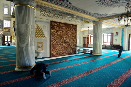 architectural style: ISTANBUL, TURKEY - 19 JANUARY  Unknown man in the Tunahan Mosque a prayer in Istanbul, Turkey on january 19, 2014  Mosque was made in 2004, made a big Ottoman architectural style of worship