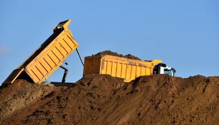 dumps: Heavy dump trucks unloading soil on the sand Stock Photo