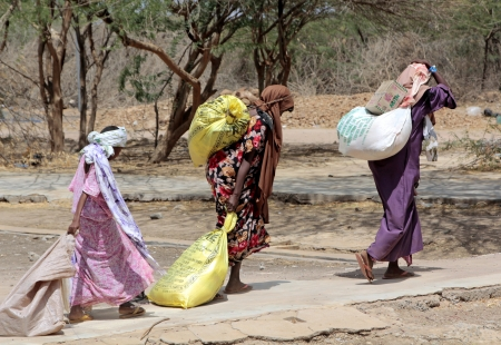 DADAAB, SOMALIA - AUGUST 8  The Dadaab refugee camp, hundreds of thousands of difficult conditions, Somali immigrants are staying  African women carrying the help they receive to their homes  August 8, 2011 in Dadaab, Somalia  Editorial