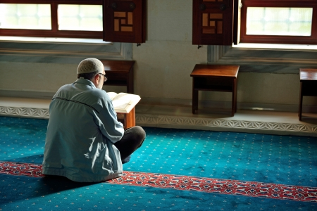 beanies: ISTANBUL, TURKEY - 19 JANUARY  Unknown man in the Tunahan Mosque a read Quran in Istanbul, Turkey on january 19, 2014  Tunahan mosque was made in 2004