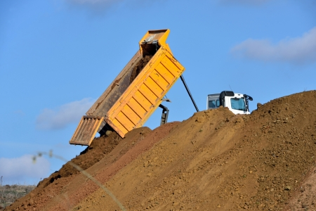 Heavy dump truck unloading soil on the sand photo
