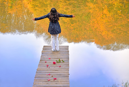happy young girl on a wooden bridge photo