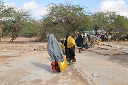 DADAAB, SOMALIA - AUGUST 8  The Dadaab refugee camp, hundreds of thousands of difficult conditions, Somali immigrants are staying  African people carrying the help they receive to their homes  August 8, 2011 in Dadaab, Somalia