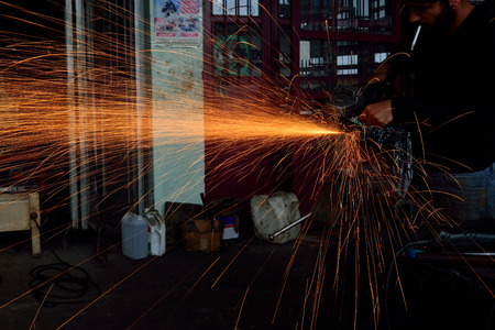 MERSIN, TURKEY - JUNE 11  Electric machine, iron cutting undefined male employees on June 11, 2014 in Mersin, Turkey  Iron working industry is one of the most heavy-duty jobs