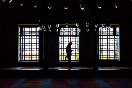 ISTANBUL, TURKEY - JULY 15  Suleymaniye mosque muslim prayers in front of the window, 15 July 2014 in Istanbul Turkey  The Suleymaniye Mosque is the largest mosque in the city, and one of the best-known sights of Istanbul