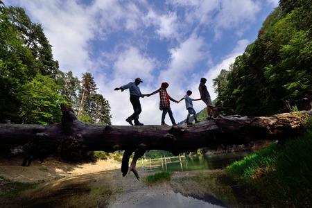 family walking on fallen tree in balance Stockfoto