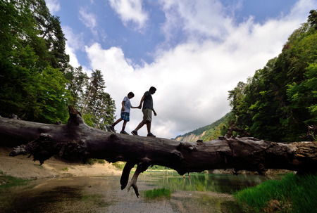 Young Adult and child Balancing on a dead Tree in Nature