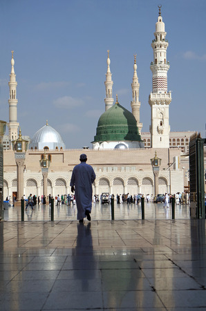 MEDINA, KINGDOM OF SAUDI ARABIA (KSA) - JAN 30: Pilgrims pray outside Masjid Nabawi after morning prayer Jan 30, 2015 in Medina, KSA. Underneath the green dome where Prophet Muhammad is laid to rest. Editorial