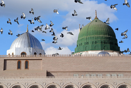 muhammed: Prophet Muhammed holy mosque and pigeons flying in the sky in Medina, KSA Stock Photo