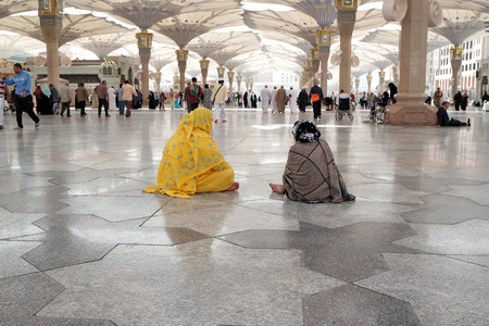 MEDINA, SAUDI ARABIA (KSA) - JAN 30: Two pilgrims woman sitting in the courtyard of the mosque of the Prophet on January 30, 2015 in Medina, KSA. Tents in the form of custom made umbrella to protect from the heat.