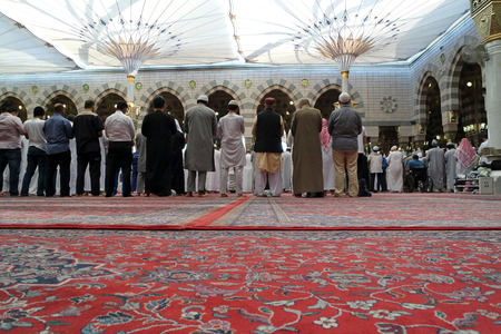 worshiped: MEDINA, KINGDOM OF SAUDI ARABIA (KSA) - JAN 31: Muslims praying in Masjid Nabawi on January 31, 2015 in Al Madinah, S. Arabia. Nabawi mosque is the 2nd holiest mosque in Islam.