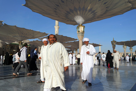 worshiped: MEDINA, KINGDOM OF SAUDI ARABIA (KSA) - JAN 30: In the prophetic mosque courtyard, walking Muslims on January 30, 2015 in Medina, KSA. Masjid Nabawi is visiting hundreds of thousands of Muslims every year. Editorial