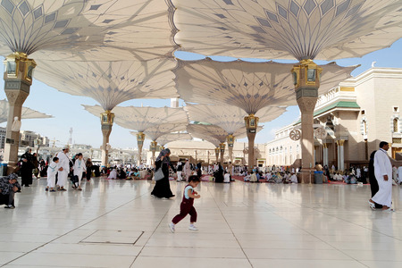 ksa: MEDINA, SAUDI ARABIA (KSA) - JAN 30: People in the courtyard of the mosque of the Prophet on January 30, 2015 in Medina, KSA. Tents in the form of custom made umbrella to protect from the heat.