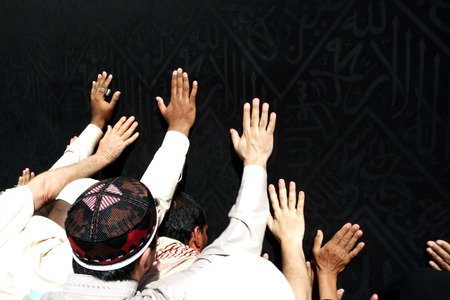 skullcap: Kaaba Mecca in Saudi Arabia and Muslim pilgrims coming for Hajj. Unidentified Muslims hand touching the black Cover.