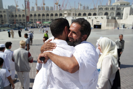 assume: MECCA, SAUDI ARABIA - FEBRUARY 4: Two Muslims greet each other at the kaaba on February 4, 2015 in Mecca, Saudi Arabia. Muslim people praying together at holy place.