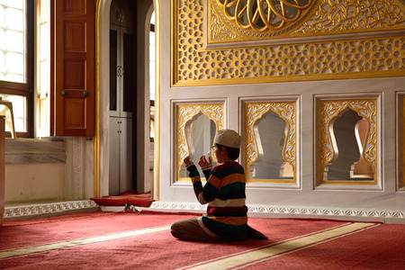 skullcap: Young praying alone in front of window