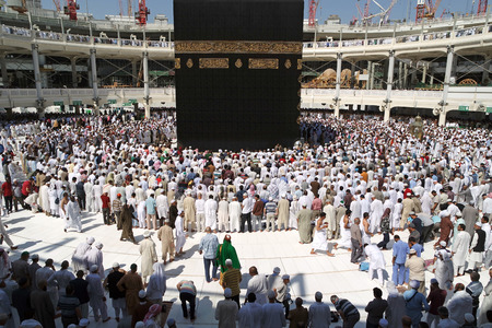 erecting: MECCA SAUDI ARABIA  FEBRUARY 4: Muslim pilgrims from all around the World revolving around the Kaaba on February 4 2015 in Mecca Saudi Arabia. Muslim people praying together at holy place.
