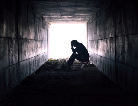 depressed man sitting in the tunnel Stock Photo
