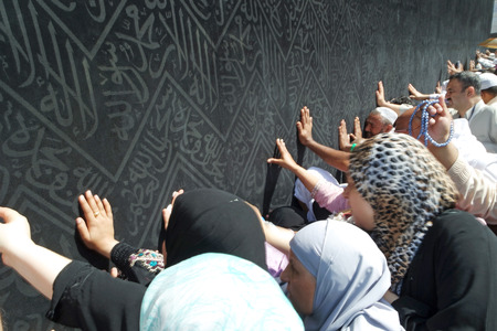 Kaaba Mecca in Saudi Arabia and Muslim pilgrims coming for Hajj. Unidentified Muslims hand touching the black Cover.