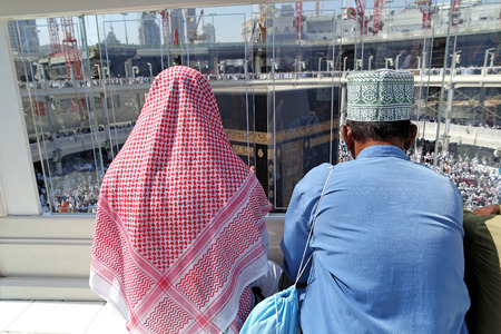 praying together: MECCA, SAUDI ARABIA - FEBRUARY 2: Muslims praying on the top floor of the Kaaba on February 2, 2015 in Mecca, Saudi Arabia. Muslim people praying together at holy place.