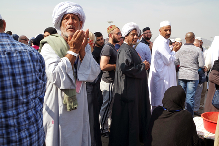 overthrown: MECCA, SAUDI ARABIA - FEB 3: Muslims praying at Mount Arafat or Jabal Rahmah February 3, 2015 in Arafat, Saudi Arabia. This is the place where Adam and Eve met after being overthrown from heaven.