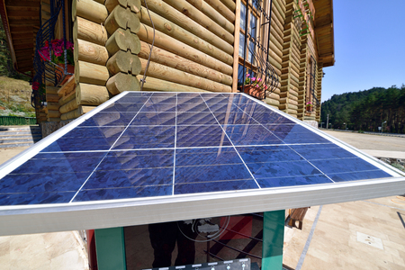 environmentalists: wooden house in front of solar panels