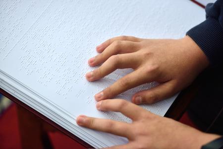 braille: Blind child read book written in Braille Stock Photo