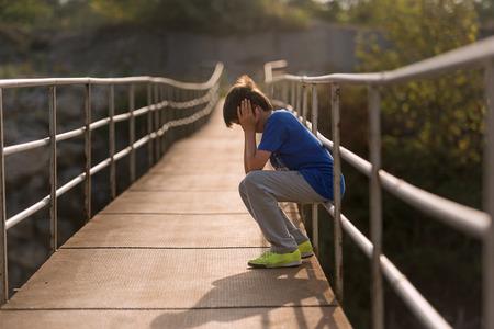 helpless: alone sitting in a sad way helpless child Stock Photo