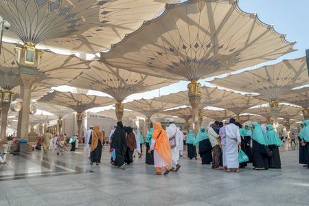 MEDINA, SAUDI ARABIA KSA - JAN 30: Muslims from different countries in the courtyard of the mosque of the Prophet on January 30, 2015 in Medina, KSA. Tents in the form of custom made umbrella to protect from the heat.