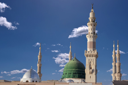 Exterior view of minarets and green dome of a mosque taken off the compound. 스톡 콘텐츠