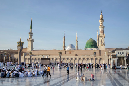 MEDINA, KINGDOM OF SAUDI ARABIA KSA - JAN 31: Muslims marching in front of the mosque of the Prophet Muhammad on January 31, 2015 in Medina, KSA. Prophet's tomb is under the green dome.