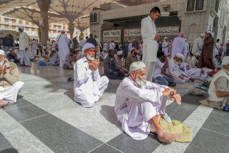 ksa: MEDINA, KINGDOM OF SAUDI ARABIA KSA - JAN 31: Pilgrims pray outside Masjid Nabawi after morning prayer Jan 31, 2015 in Medina, KSA. The mosque is the second holiest mosque in Islam.