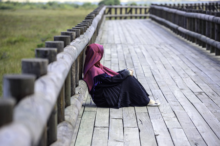 Muslim girl sitting on a wooden path Stock Photo