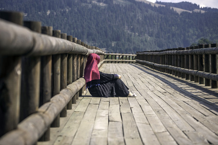 considerate: Muslim girl sitting on a wooden path Stock Photo
