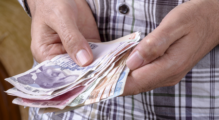 public servants: Turkish lira held on a white background Stock Photo