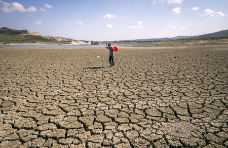 desert ecosystem: with a red ball in his hand walking child walking on dry land Stock Photo