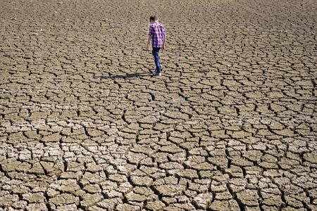 desert ecosystem: children walking on dry cracked surface Stock Photo