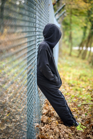 distraught: wire fence in front sad young man standing